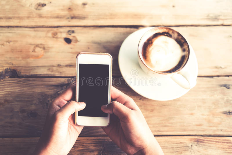 Beautiful young hipster woman`s hands holding mobile smart phone with hot coffee cup at cafe shop royalty free stock photography