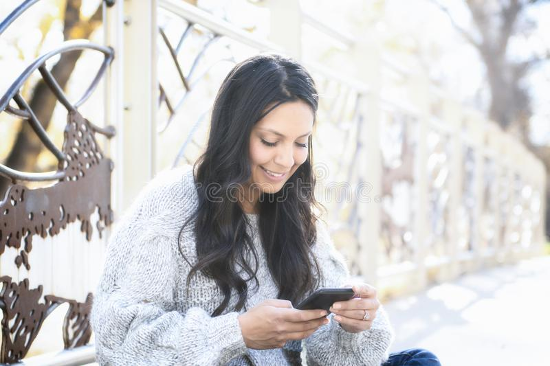 Beautiful Young Hispanic, American Indian, Multi-racial Woman with Cell Phone. Beautiful Young Hispanic, American Indian, Multi-racial Woman Checking Messages & stock photos