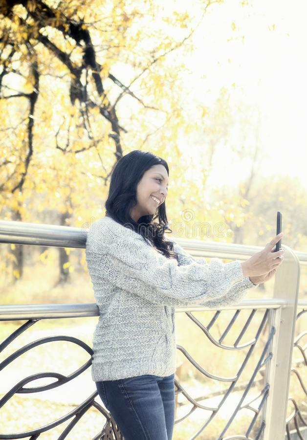 Beautiful Young Hispanic, American Indian, Multi-racial Woman with Cell Phone. Beautiful Young Hispanic, American Indian, Multi-racial Woman Checking Messages & stock images
