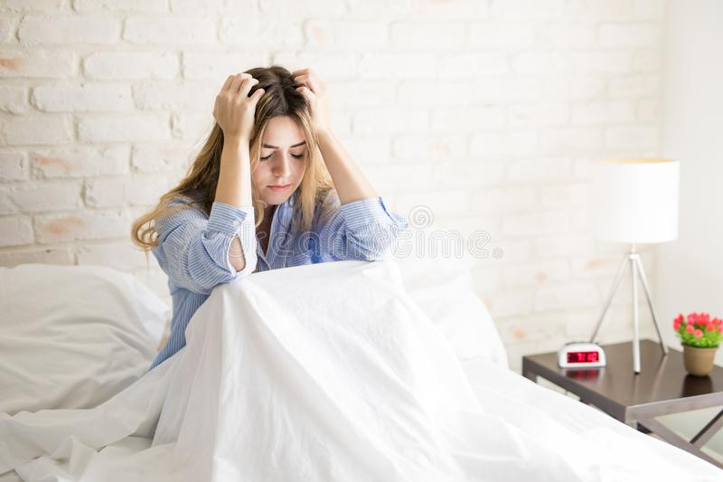 Woman feeling stressed in bed royalty free stock photography