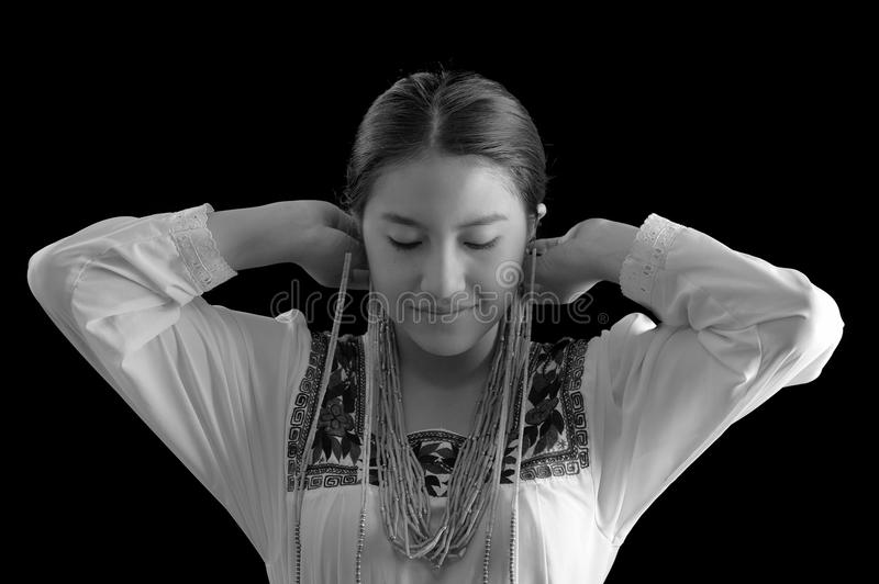 Beautiful young hispanic woman wearing light colored blouse with traditional embroided edges, attaching typical. Indigenous necklace herself while smiling, dark stock images