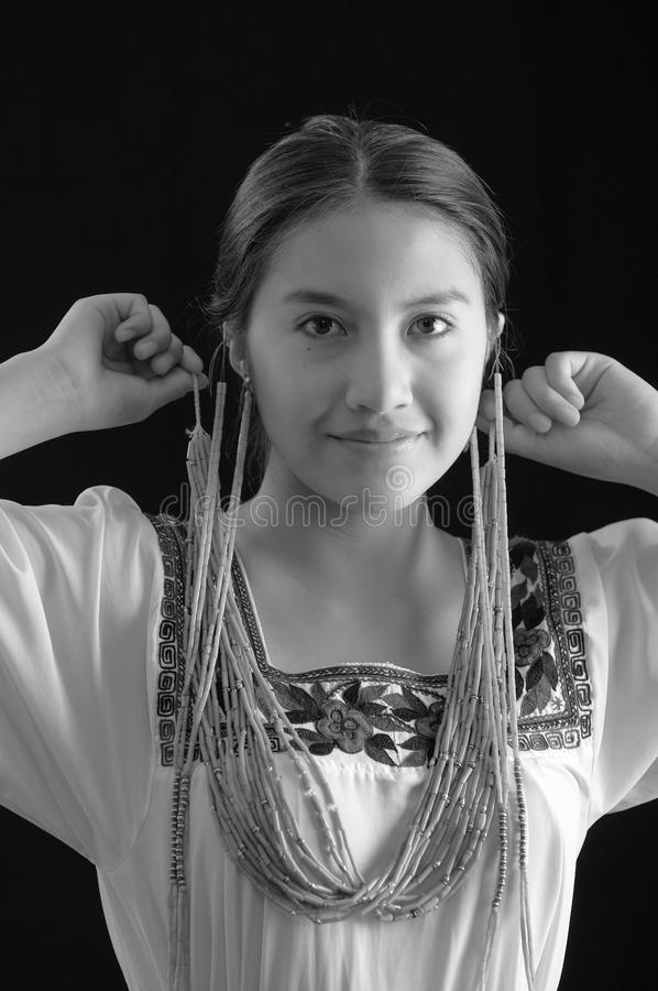 Beautiful young hispanic woman wearing light colored blouse with traditional embroided edges, attaching typical. Indigenous necklace herself while smiling, dark stock photo