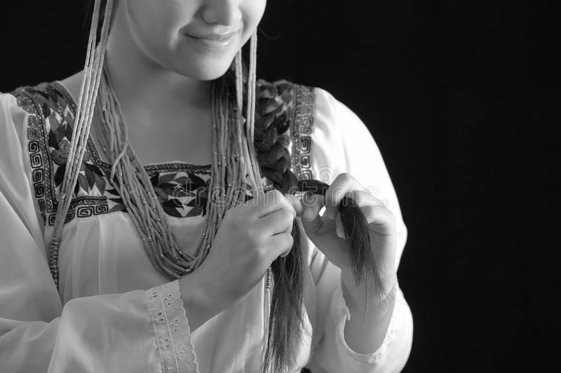 Beautiful young hispanic woman wearing light colored blouse with traditional embroided edges, braiding her own hair. While smiling, dark studio background royalty free stock photo