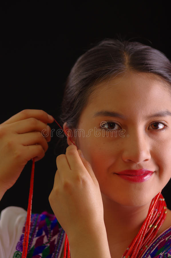 Beautiful young hispanic woman wearing white blouse with traditional embroided edges, attaching red hair extensions. Herself and smiling, black studio stock photography