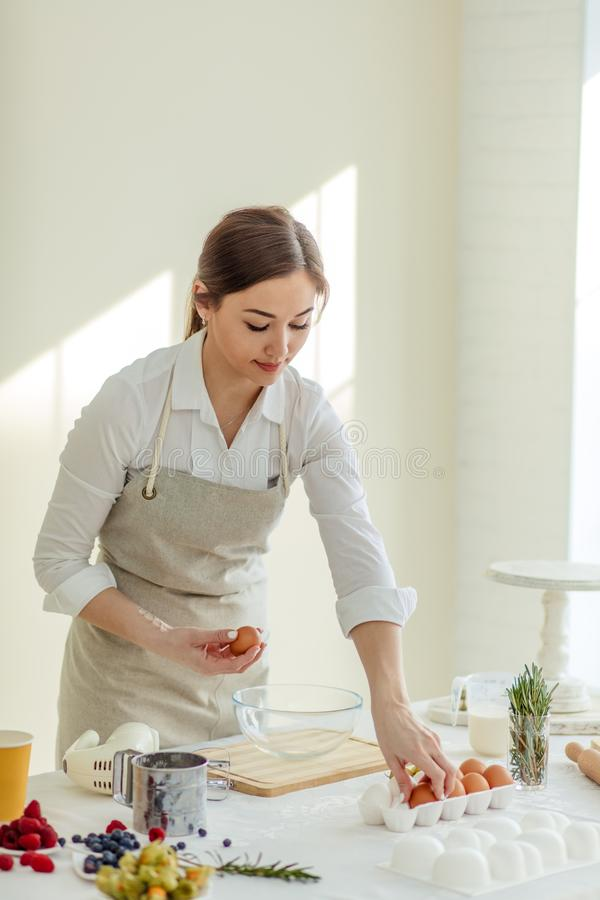 Beautiful young housewife holding eggs for making breakfast for family stock photography