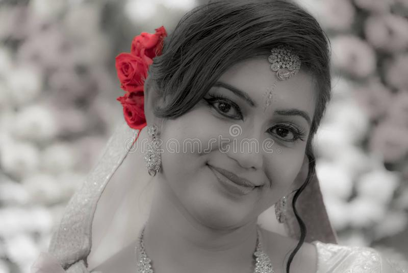 A beautiful young indian bride in bridal makeup with eyes at the camera in black and white with selective red colored rose royalty free stock photo