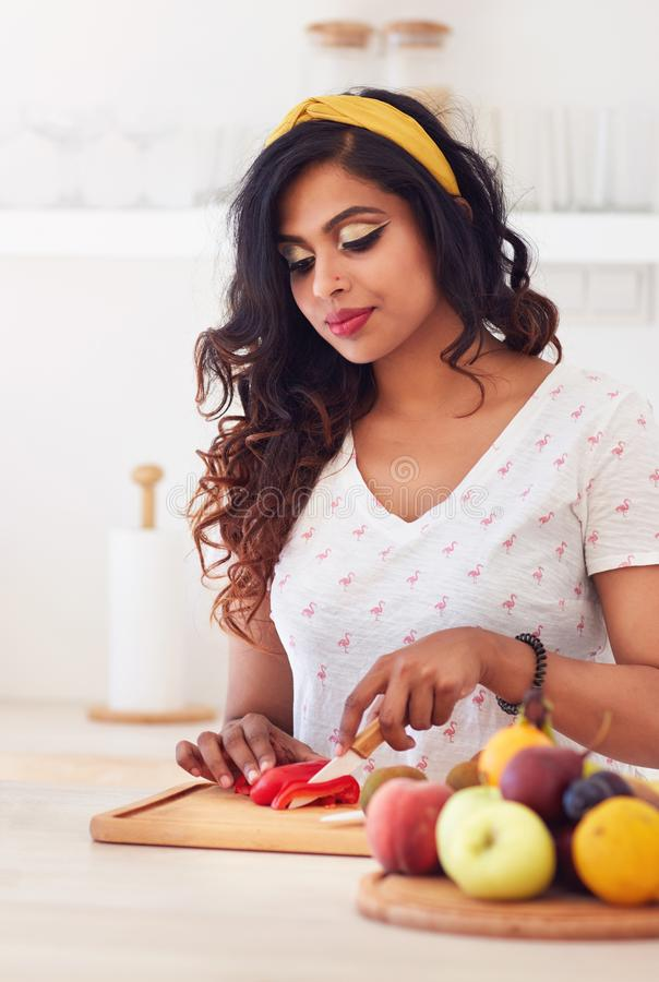 Beautiful young indian woman cutting vegetables on the kitchen, healthy eating stock image