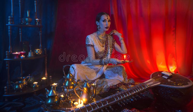 Beautiful young indian woman in traditional Sari clothing and Oriental Jewelry with candle stock photos