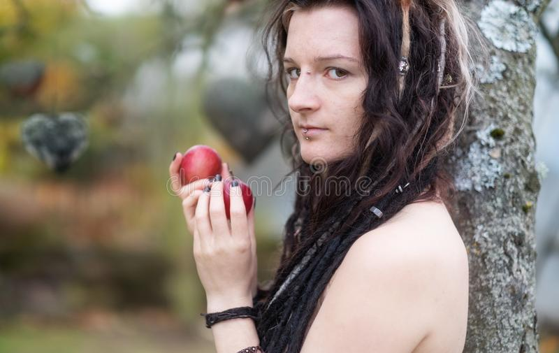 Beautiful young individual, eccentric woman, with attractive dreadlocks, piercing and tattoo showing in the garden of Eden stock images