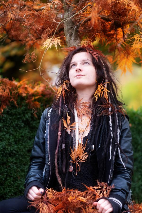 Beautiful young individual, eccentric woman, with dreadlocks, piercing and tattoo, wearing a black leather jacket, sits stock image
