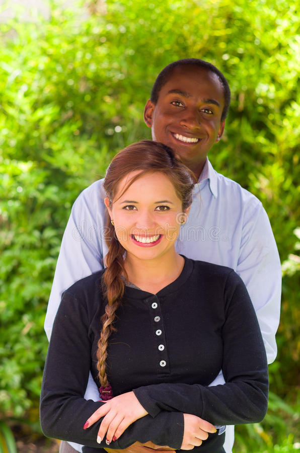 Beautiful young interracial couple in garden environment, embracing and smiling happily to camera royalty free stock photography