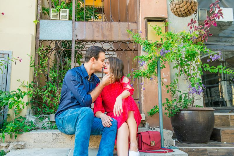 Beautiful young kissing couple sitting on the stairs on mediterranean city street. Love, dating, romance, joy and happiness. Lifes royalty free stock photos