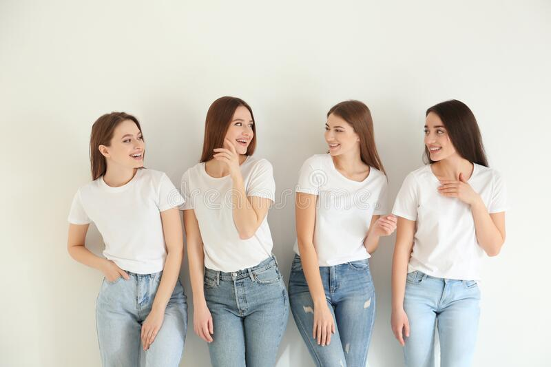 Beautiful young ladies in jeans and white t-shirts on background. Woman`s Day. Beautiful young ladies in jeans and white t-shirts on light background. Woman`s royalty free stock photography