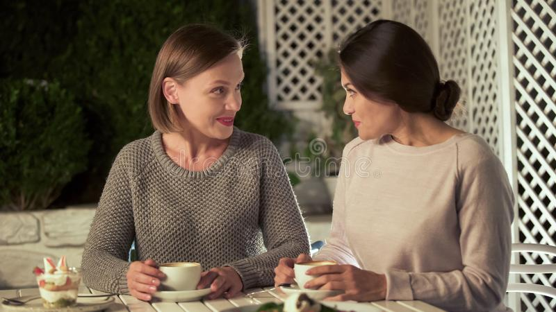 Beautiful young ladies talking in cafe, female friends spending time together royalty free stock photo