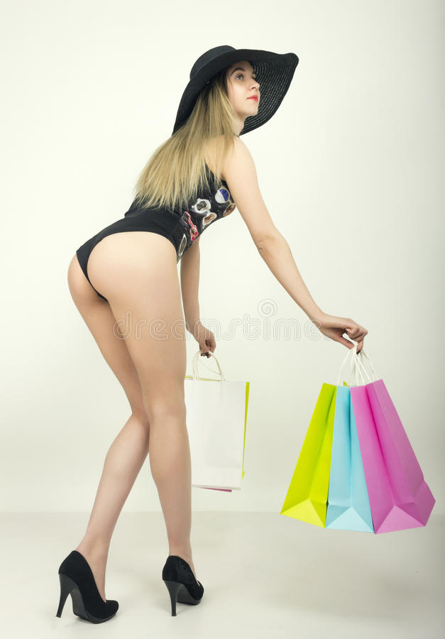 Beautiful young lady in a bathing suit, big black hat on high heels, holding colorful bags. Girl goes shopping royalty free stock image