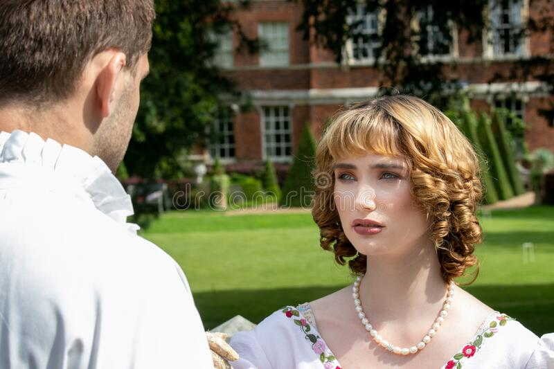 Beautiful young lady dressed in period costume confronting her husband or lover with stately home in background. royalty free stock image