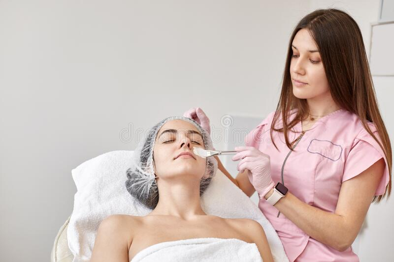 Beautiful young lady having face lifting massage, brunette woman lying on couch with closed eyes, wearing white towel and medical stock image