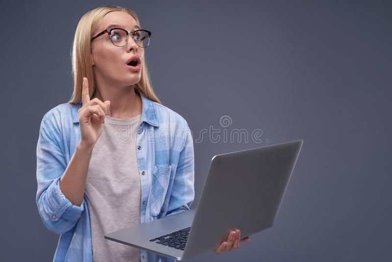 Beautiful young lady having good idea while using laptop royalty free stock image
