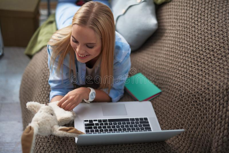 Charming blond girl looking at cute toy while resting at home royalty free stock photo