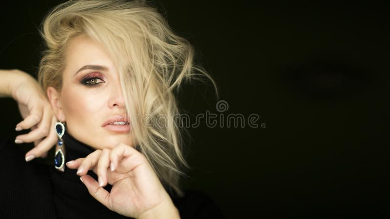 Beautiful young lady with make up face. Close-up of an attractive girl of European appearance on dark background. royalty free stock photos