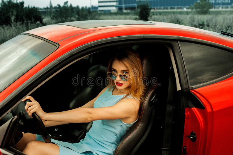 Beautiful young lady in red car. Horizontal portrait of beautiful young lady in sunglasses sits in red car and looking at the camera royalty free stock photos