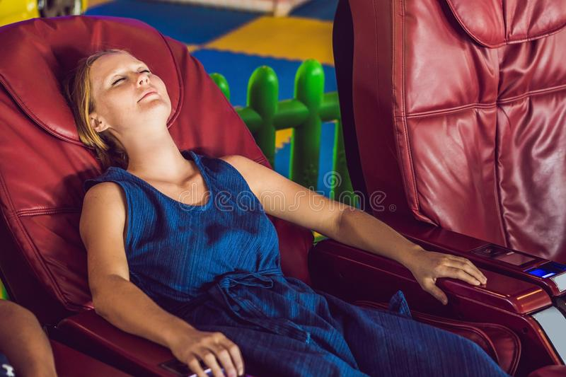 Beautiful young lady relaxing in the massage chair royalty free stock photos
