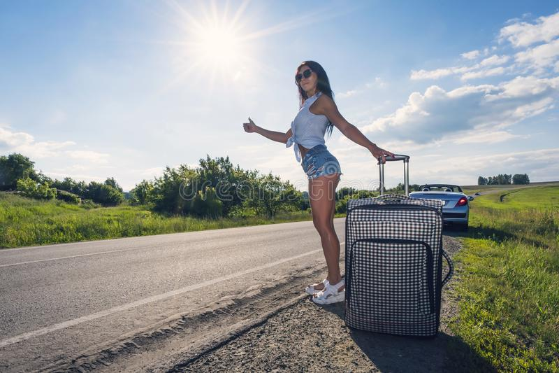 Beautiful young lady on rural road with suitcase hitchhiking on sunny day outdoors landscape backround. woman stretched royalty free stock photos