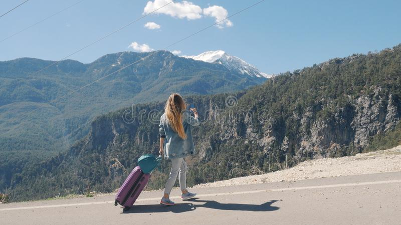 Beautiful young lady on rural road with suitcase hitchhiking on sunny day outdoors royalty free stock photography