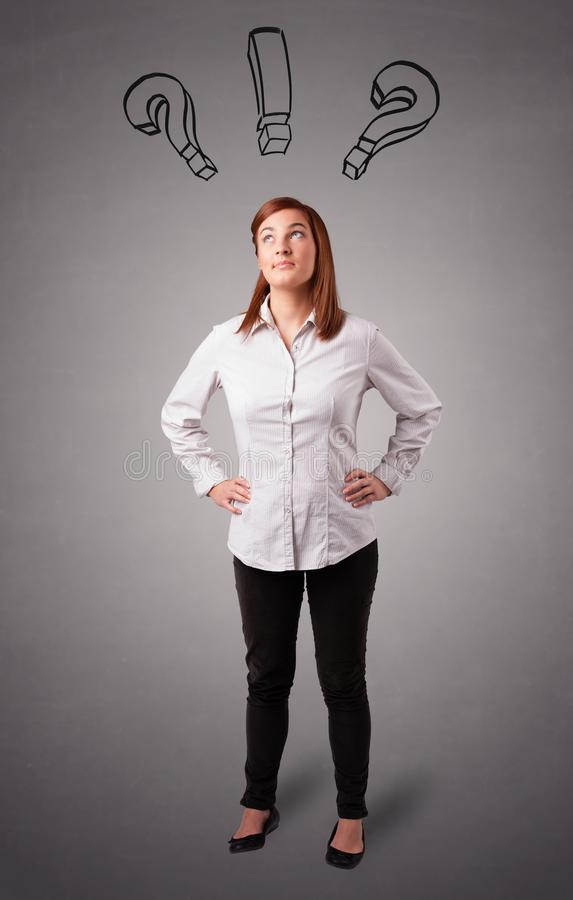 Young lady thinking with question marks overhead. Beautiful young lady thinking with question marks overhead stock photography