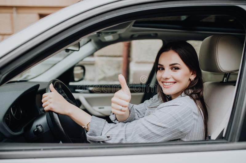 Beautiful young woman driving her brand new car and showing her thumb up stock image