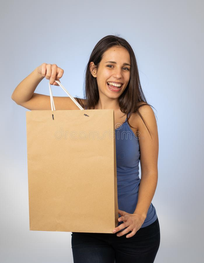 Beautiful young latin woman holding paper shopping bag with copy space royalty free stock image