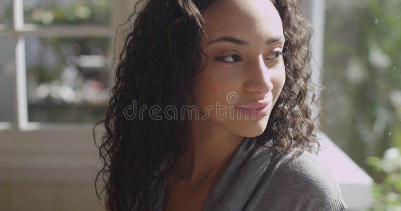 Beautiful young latino woman looking out a window stock photo