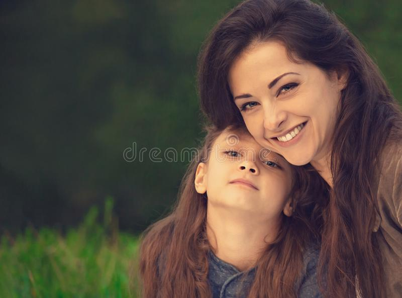 Beautiful young laughing mother embracing her cute long hair daughter on summer green grass background. Portrait of picnic royalty free stock images