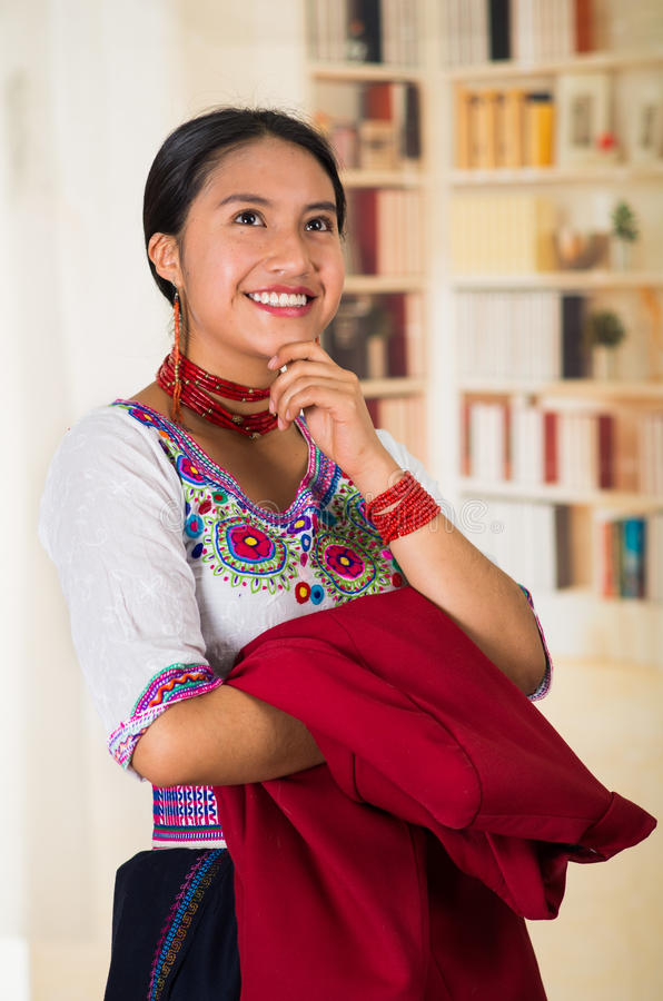 Beautiful young lawyer wearing traditional andean blouse, holding red jacket smiling to camera, bookshelves background royalty free stock image