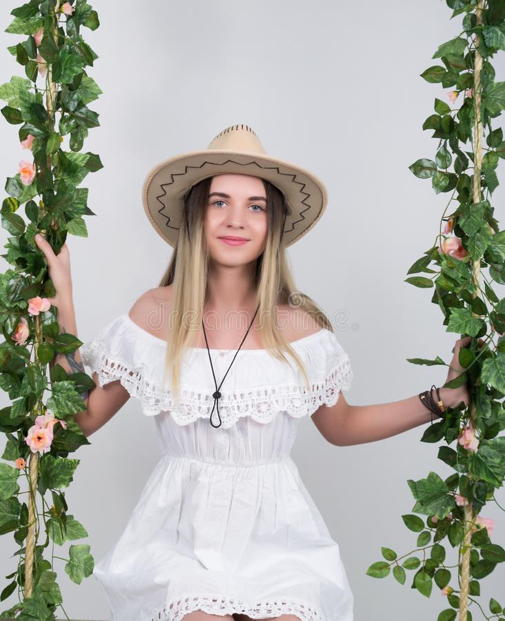 Beautiful young leggy blonde in a little white dress and white cowboy hat on a swing, wooden swing suspended from a rope stock photo