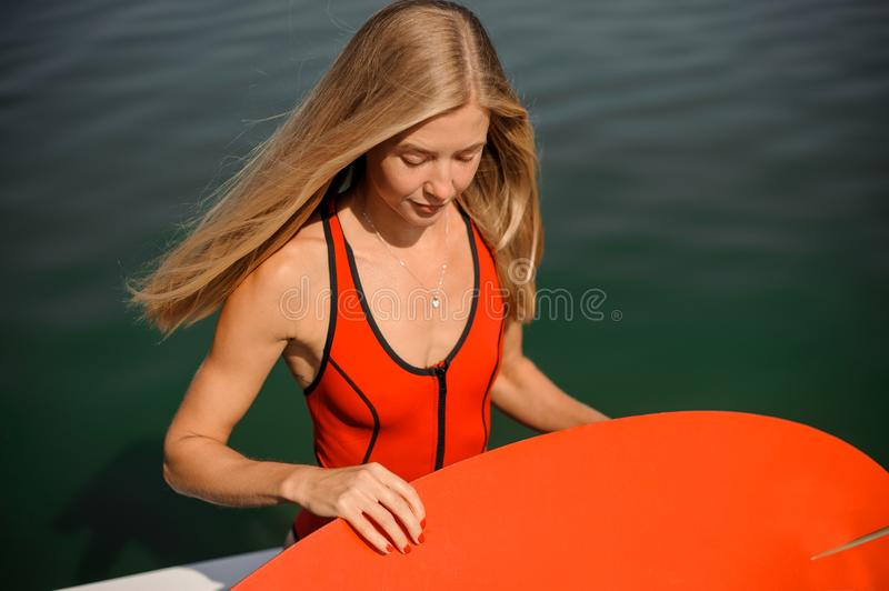 Beautiful long-haired blonde woman holding a wake board stock photography