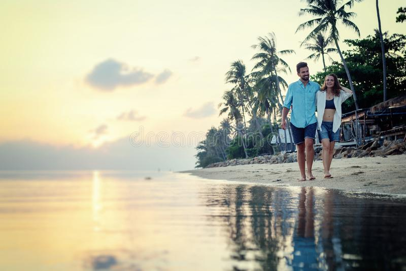 Beautiful young love happy couple walking arm in arm on the beach at sunset during the honeymoon vacation travel royalty free stock photography