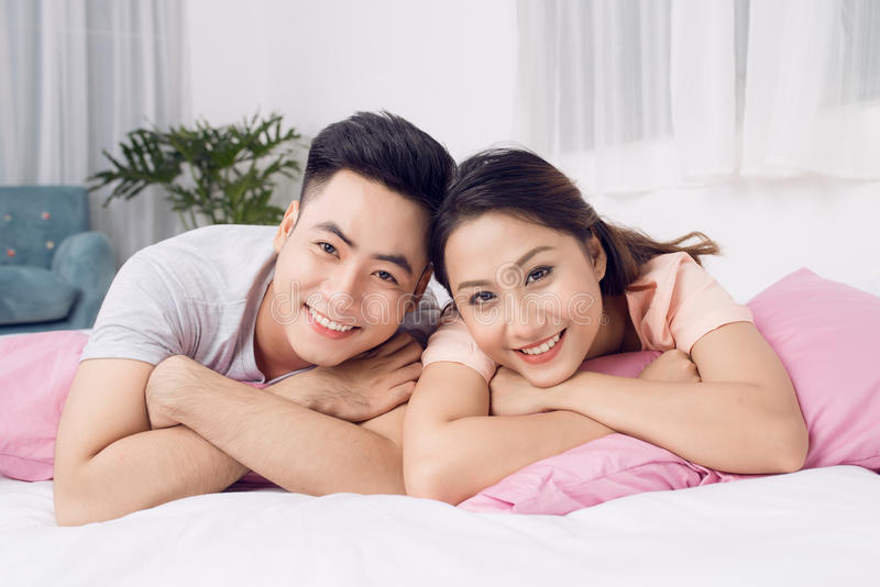 Beautiful young loving couple lying in bed together royalty free stock photo