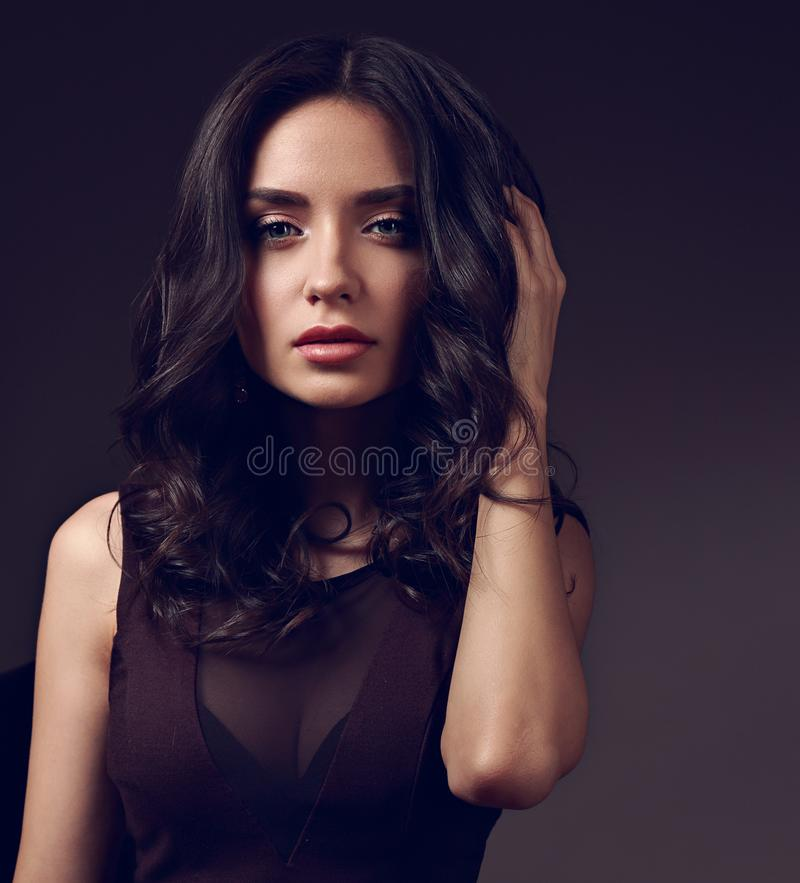 Beautiful young makeup brunette model with curly hairstyle looking calm on dark shadow background. Closeup toned portrait royalty free stock image