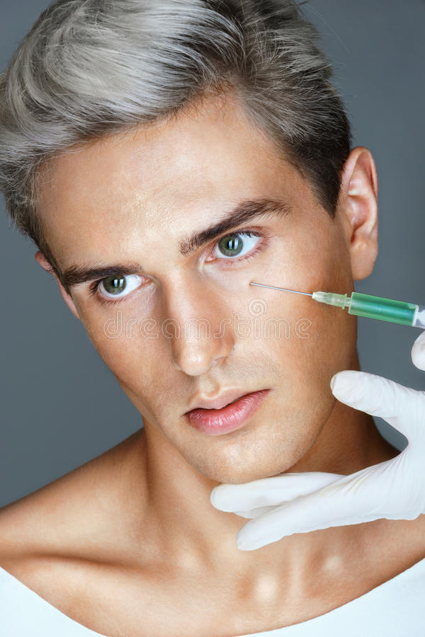 Beautiful young man gets beauty injection in eye area from nurse. stock image