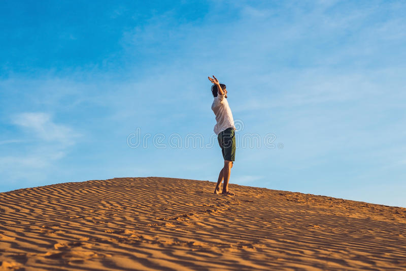 Beautiful young man jumping barefoot on sand in desert enjoying royalty free stock photos