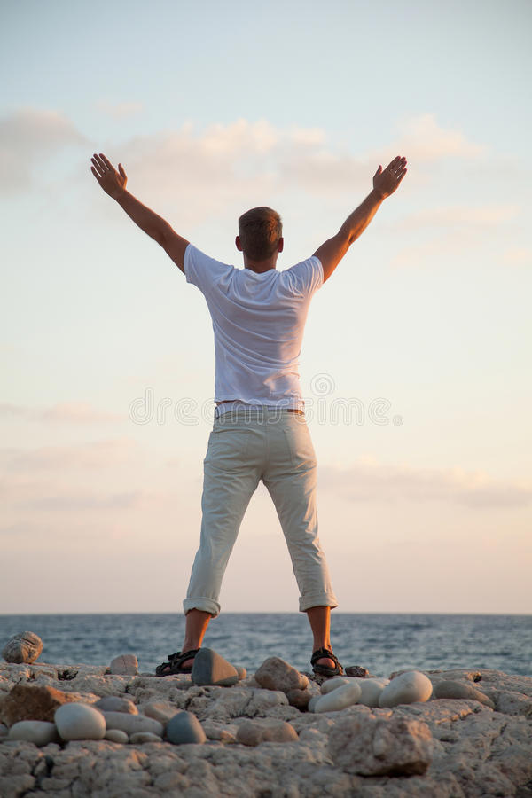 Beautiful young man on the seashore. At daybreak stock photos