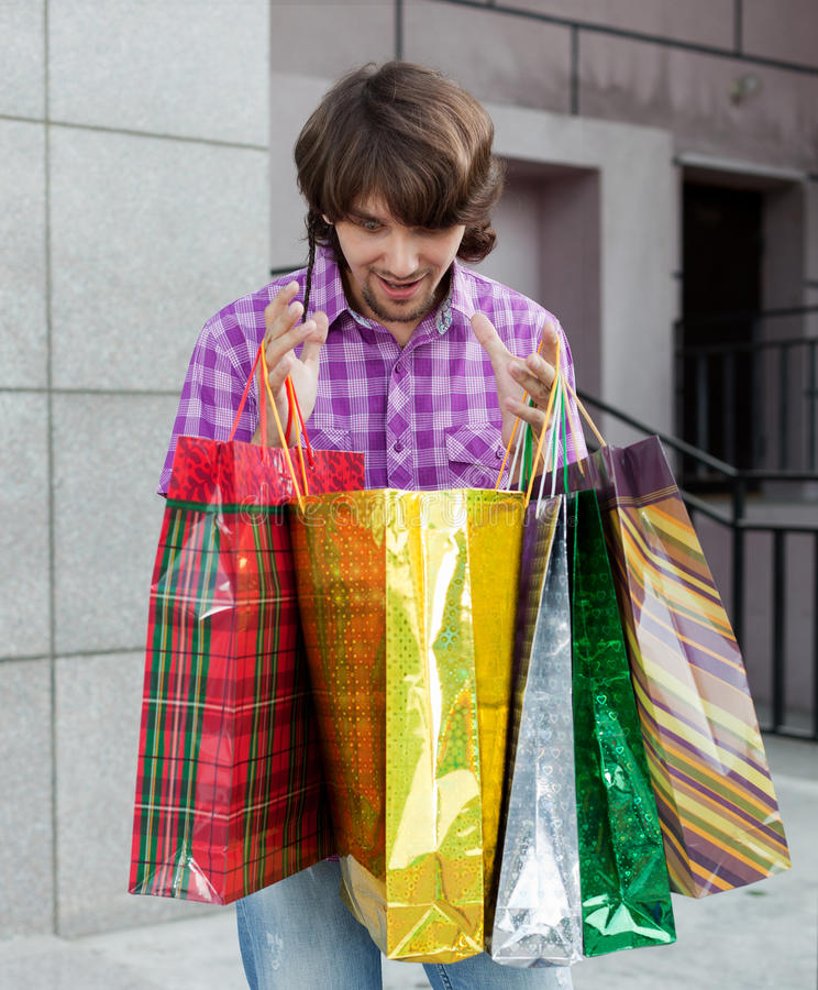 Beautiful young man after shopping royalty free stock images