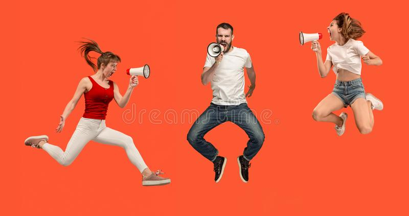 Beautiful young man and woman jumping with megaphone isolated over red background stock image