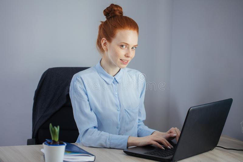 Portrait of redhaired young woman with laptop sitting at the tab stock photos