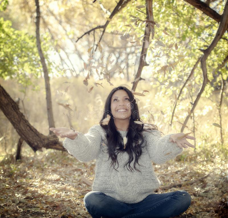 Beautiful Young Millennial Hispanic, American Indian, Multi-racial Woman Throwing Leaves. Outside on a Fall Day royalty free stock photography
