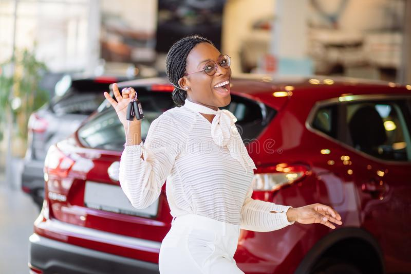African woman with her new car showing key royalty free stock photo