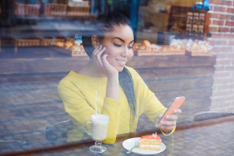 Beautiful young mixed race woman seen through the window of bakery stock photos