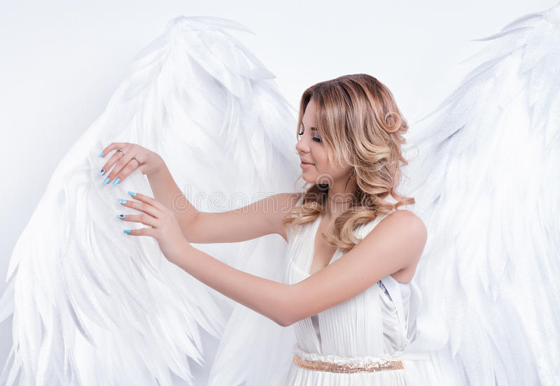 Beautiful young model with big angel wings posing royalty free stock images