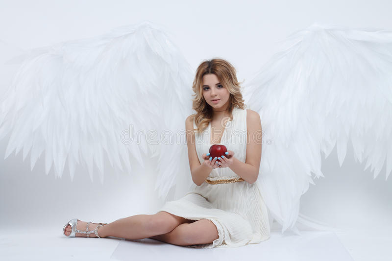 Beautiful young model with big angel wings sitting in the studio stock photography